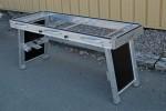 La surface libérée des éléments de serrage peut être utilisée pour la coupe de panneaux ou servir de table avec les deux plateaux logés dans les piétements.